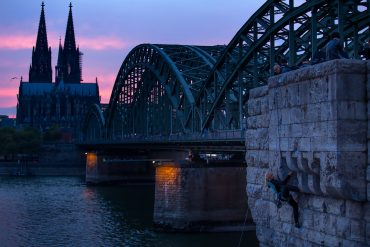 Rock climbing along the Rheine, Cologne Cathedral in the background.