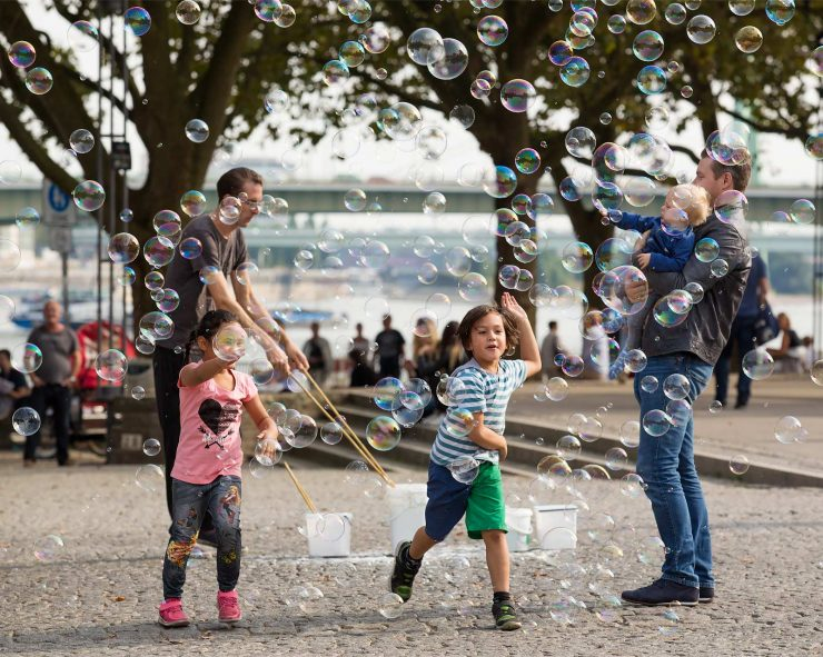 Children chase bubbles below in a riverside park in Cologne.