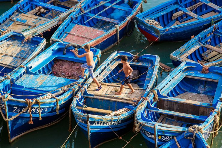 Two boys run across moored, bright blue fishing boats before jumping into the water in the Essaouira harbor.