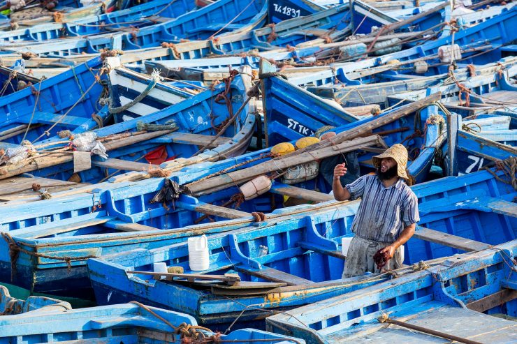 fisherman and blue boats in Essaouira, Morocoo