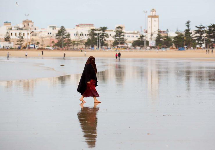 Woman in burkha on the beach