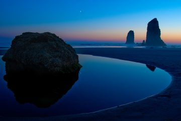 Photo of sea stacks and sunset reflected in tide pool at Canon Beach.