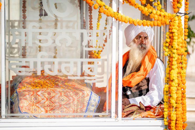 Old man with beard and turban in a glass box covered with marigold garlands