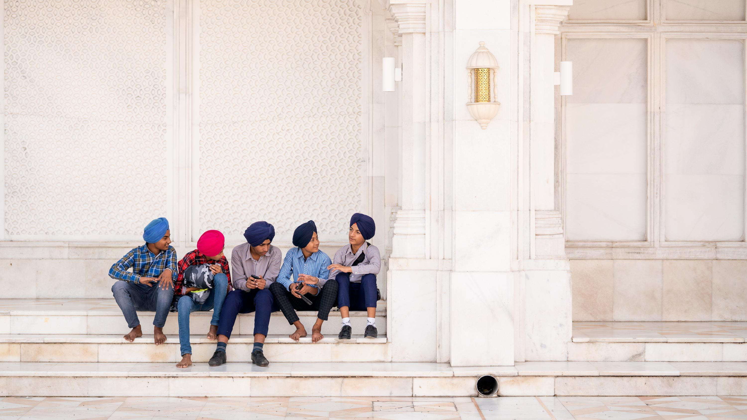 A group of boys in western clothes and turbans in a row on white marble steps